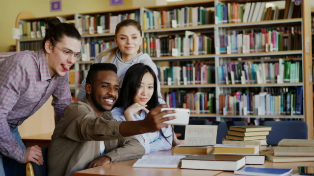 Group-of-international-students-have-fun-smiling-and-making-selfie-photos-on-smartphone-camera-at-university-library-Cheerful-friends-have-rest-while-prepare-for-examination