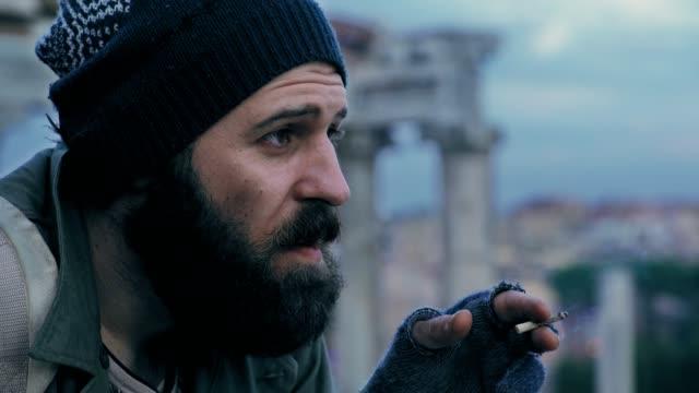 close-up-on-homeless-man-lights-a-cigarette-butt:-misery-poorness