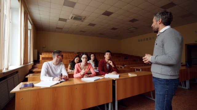 Professor-ist-Frage-und-auf-Studenten-warten-auf-Antwort-zeigen-sind-junge-Menschen-Hände-erhebend-und-sprechen-Die-Überprüfung-der-Kenntnisse-und-Lehrkonzept-