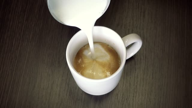 Preparation-process-of-coffee-with-shaked-up-milk---latte-or-cappuccino-in-white-cup-Closeup-view