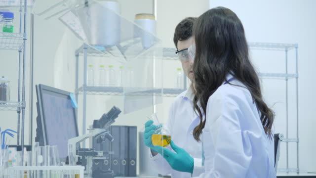Dos-científicos-de-la-investigación-médica-trabaja-con-muestras-en-caja-de-aislamiento-en-el-laboratorio-moderno