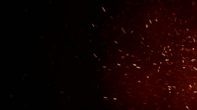 Ardiente-caliente-chispas-de-fuego-grande-en-el-cielo-de-la-noche-Movimiento-de-lado-Resumen-fuego-aislado-brillantes-partículas-en-cámara-lenta-de-fondo-negro-Bucle-de-animación-en-3d-