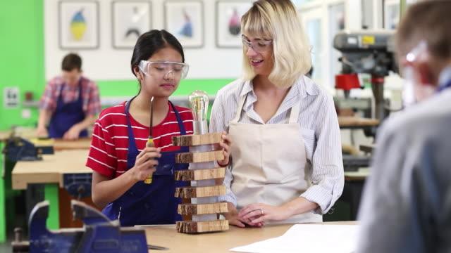 Lehrer-helfen-weiblich-High-Student-Schulgebäude-Lampe-In-Holzarbeiten-Lektion