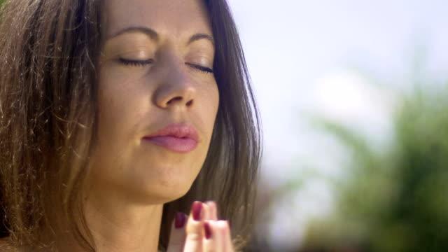 Oración-de-la-mujer-tiene-manos-en-pose-de-namaste-lectura-mantra-oración-parque-al-aire-libre