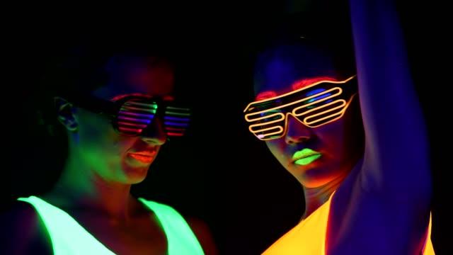 Frauen-mit-UV-Bemalung-leuchtende-Kleidung-leuchtende-Armband-Gläser-tanzen-vor-der-Kamera-Gesicht-geschossen-Kaukasische-und-Frau-