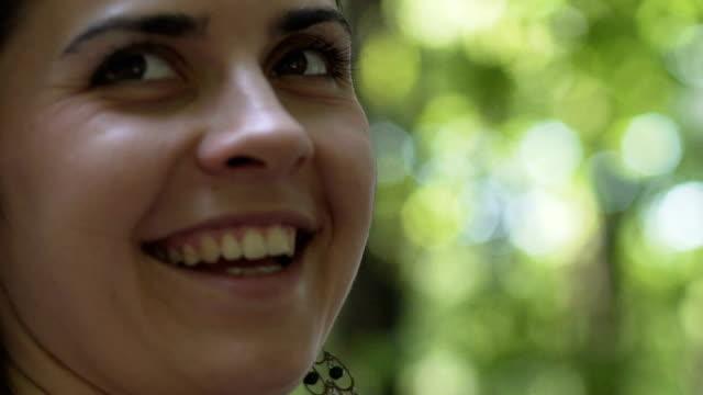 Sonriente-mujer-de-caminatas-en-el-bosque-se-da-la-vuelta-feliz-mujer-goza-fecha-de-Parque-de-la-vida