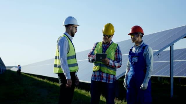 Arbeiter-reden-dazwischen-lange-Reihen-von-Sonnenkollektoren