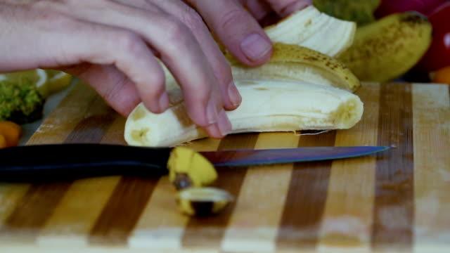 Hombre-es-poner-un-plátano-pelado-en-la-tabla-de-cortar-en-cámara-lenta