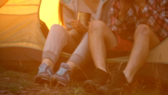 Amigos-en-calzado-cómodo-sentado-en-la-tienda-y-tomar-té-senderismo-en-el-bosque