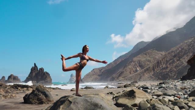 hübsche-blondes-Mädchen-in-schwarzen-Top-entspannt-sich-in-Yoga-Pose-Lotus-auf-lila-Matte-gegen-die-Wellen-des-Ozeans,-die-auf-Felsen