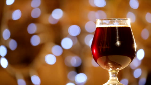 Cold-delicious-dark-beer-in-a-glass-is-spinning-on-background-of-blurred-lights-Craft-Beer-close-up-rotation-Pint-of-beer-Pub-concept