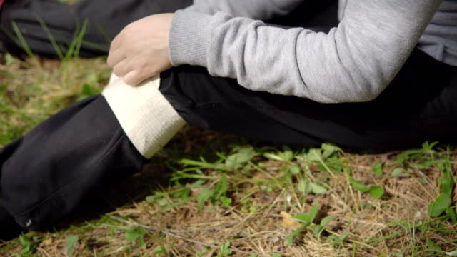 Close-up-of-winding-an-elastic-bandage-on-the-knee-Injury-in-nature