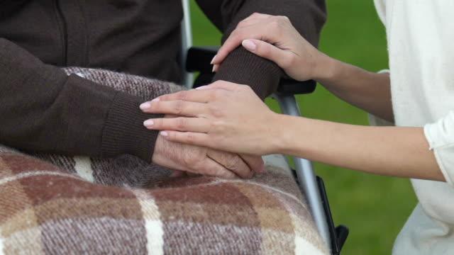 Apoyo-mujer-cogidos-de-la-mano-del-hombre-discapacitado-compasivo-cuidados-de-enfermería