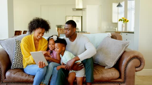 Vista-frontal-de-la-familia-black-con-tableta-digital-en-sala-de-estar-en-casa-4k