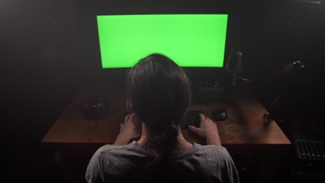 A-man-looks-at-the-green-screen-of-the-monitor-Nods-his-head-working-atmosphere-4K-Slow-Mo
