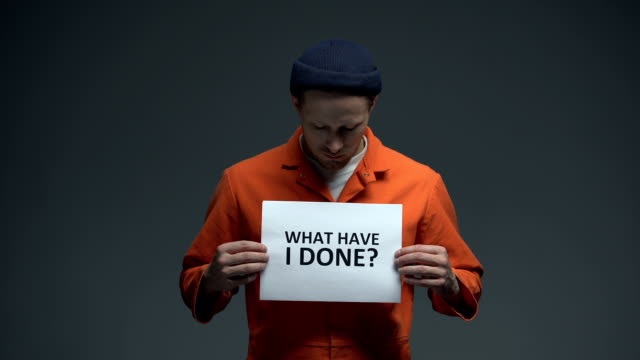 Caucásico-prisionero-varón-sosteniendo-lo-que-he-hecho-firmar-pidiendo-justicia