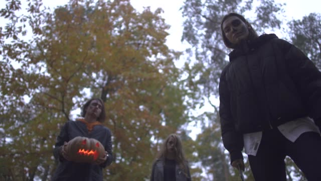 Man-and-two-young-women-in-Halloween-costumes-looking-down-on-the-victim-with-serious-scary-faces-in-autumn-park