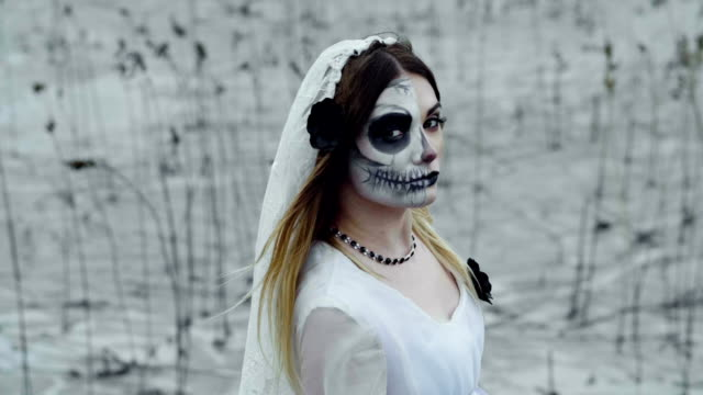 A-woman-with-spooky-make-up-for-Halloween-in-a-white-bride-dress-Slow-motion-HD