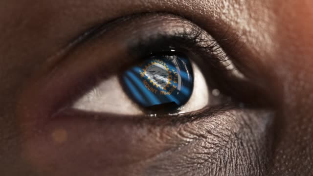 Woman-black-eye-in-close-up-with-the-flag-of-South-Dakota-state-in-iris-united-states-of-america-with-wind-motion-video-concept