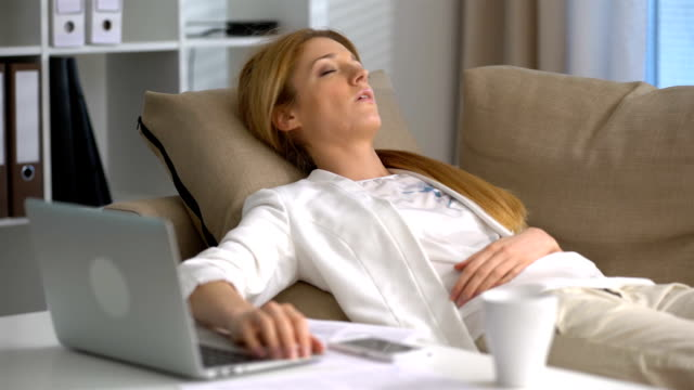 Tired-businesswoman-sleeping-on-the-couch-in-the-office-with-laptop-and-phone