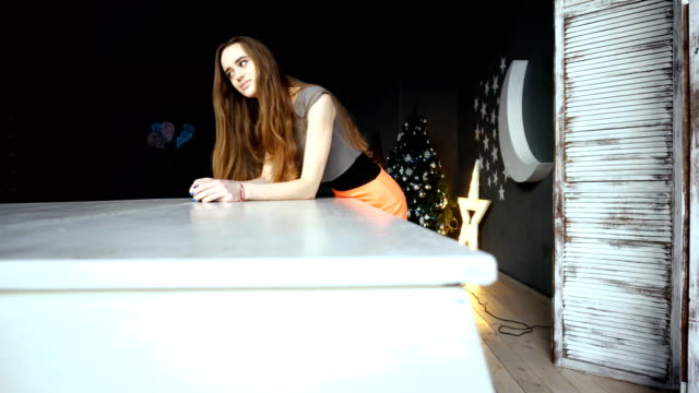 Young-woman-leaned-on-a-white-grand-piano