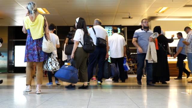 Personas-que-buscan-en-el-tablero-de-salida-de-horario-en-el-aeropuerto-internacional-Pasajeros-con-equipaje-en-la-terminal-Timelaps