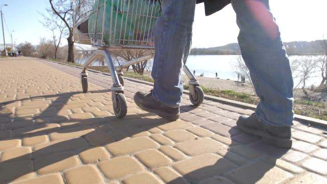 Vista-posterior-de-las-piernas-del-hombre-sin-hogar-caminando-con-el-carro