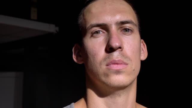 Junge-zuversichtlich-Basketballspieler-Besitz-Ball-auf-seine-Schulter-und-Blick-in-die-Kamera-mit-ernsten-Ausdruck