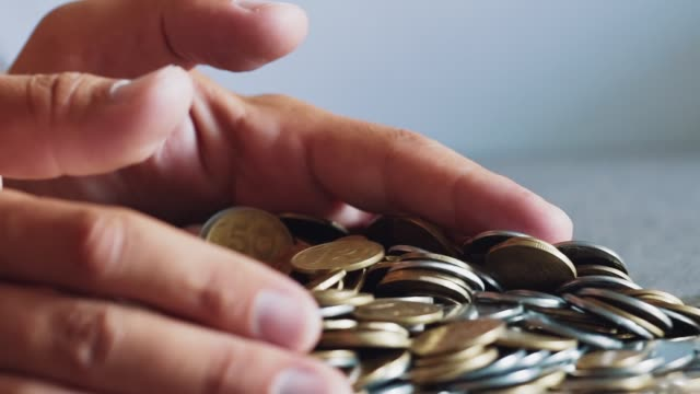 Close-up-gold-and-silver-coins-in-hand-