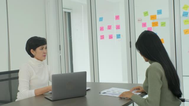 Joven-empresaria-asiática-recibiendo-la-reprimenda-de-su-mujer-jefe-en-la-oficina