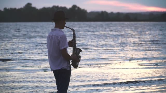 Chico-joven-guapo-es-jugar-el-saxophone-en-la-orilla-del-río