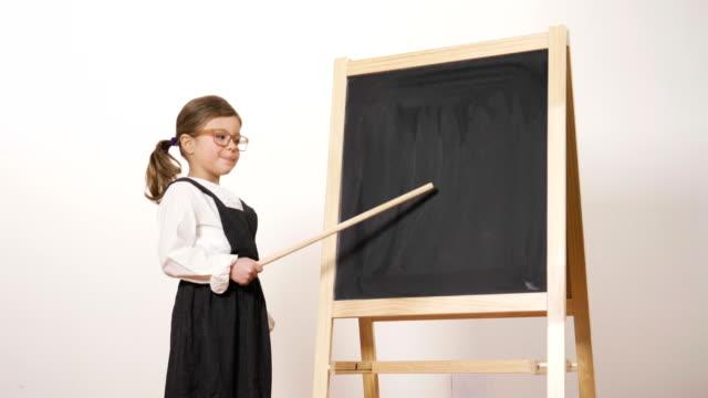 Una-chica-feliz-vestido-como-un-profesor-ante-una-pizarra-pequeña-mantiene-sus-brazos-cruzados-y-sonrisas-