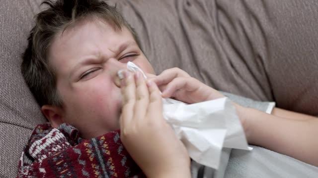 El-niño-sopla-su-nariz-en-servilletas-de-papel.-Tiene-un-resfriado