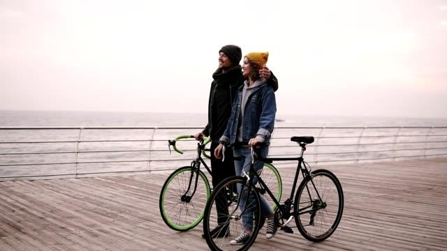 Hermosa-pareja-sonriente-de-los-hipsters-jóvenes-caminando-juntos-abrazando-con-sus-bicicletas-cerca-del-mar-en-día-de-otoño-Chica-joven-de-sombrero-amarillo-en-algo-Caminando-por-cubierta-de-madera-durante-el-día-Horizonte-de-la-mar