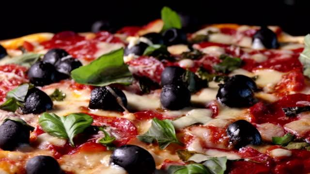 Horno-pizza-con-peperoni-salami-aceitunas-negras-albahaca-y-mozarella-queso-Spin-shot-