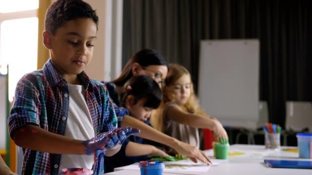 Niños-lindos-de-diversas-pintura-con-las-manos-en-la-lección