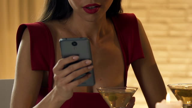 Woman-using-smartphone-in-restaurant-disappointed-with-boring-man-closeup