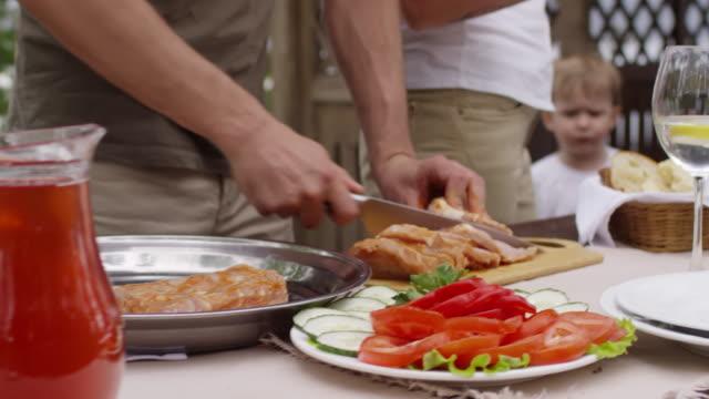Unrecognizable-Man-Preparing-Meat-for-Picnic