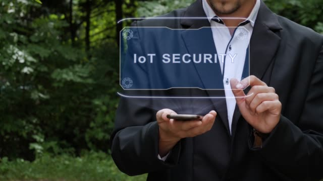 Businessman-uses-hologram-with-text-IoT-SECURITY