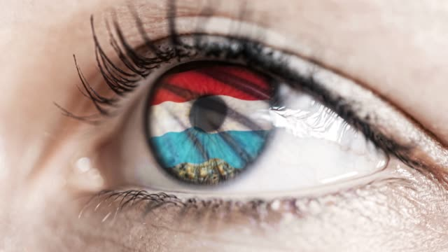 woman-green-eye-in-close-up-with-the-flag-of-Luxembourg-in-iris-with-wind-motion-video-concept