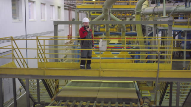 Male-Quality-Controller-Checking-Slabs-of-Rockwool-on-Conveyor-Belt
