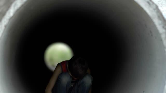 triste-solitario-muchacho-escondido-dentro-de-un-túnel-de-drenaje-lonely-boy-sin-hogar-en-depresión-profunda