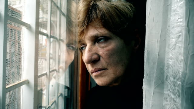 depressed-thoughtful-mature-woman-at-the-window