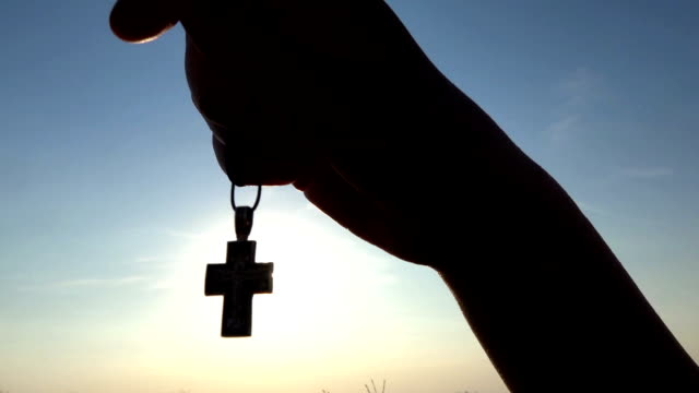Closeup-Of-Silhouette-Cross-Hanging-at-sunset/sunrise-time