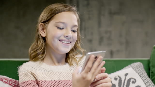 Young-girl-holding-phone-speaking-by-video-call
