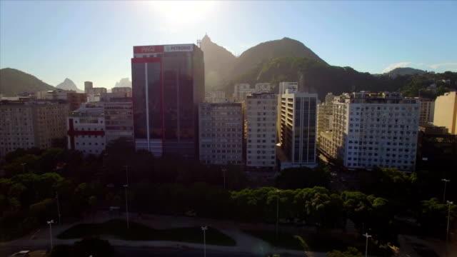 Aéreo-de-Rio-de-Janeiro:-hacia-los-lados-y-hacia-arriba-mover-en-barrio-Botafogo-revelando-Christ-Redentor-detrás-de-los-altos-edificios-al-atardecer
