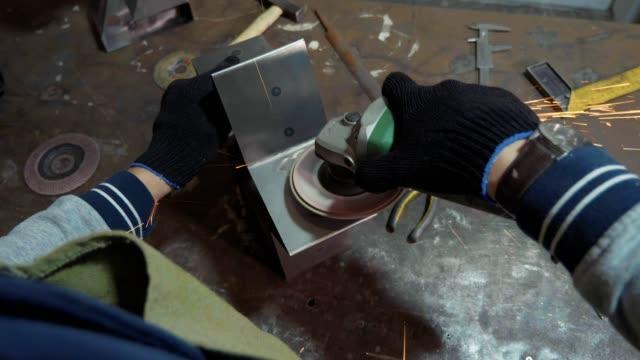 Artesano-usando-una-amoladora-para-el-pulimento-de-metal-detalle-en-taller-