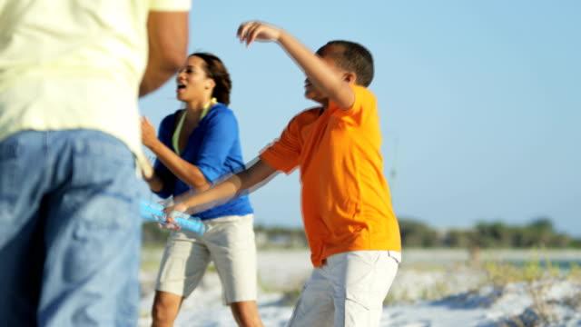 Ethnische-Eltern-und-Sohn-Baseball-zu-spielen,-am-Strand
