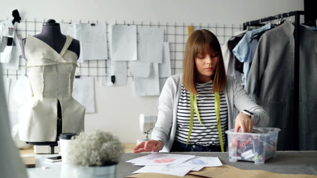 Tailor-s-shop-employee-is-choosing-threads-from-box-comparing-colors-choosing-perfect-tone-and-applying-it-to-clothing-design-sketch-Planning-future-clothes-collection-concept-