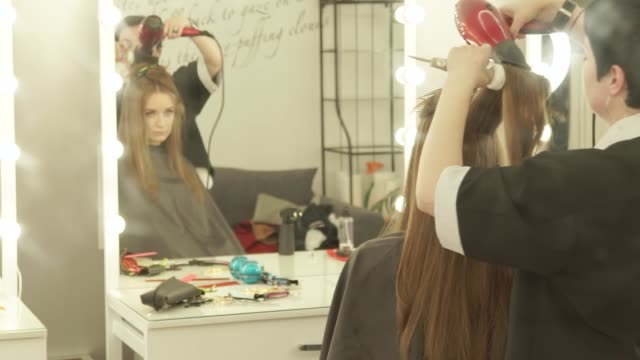 Hairstylist-making-woman-hairstyling-long-hair-with-dryer-and-brushfront-mirror-in-dressing-room-Close-up-hairstyling-woman-hair-with-dryer-and-hairbrush-after-washing-and-cutting-in-hairdressing-salon